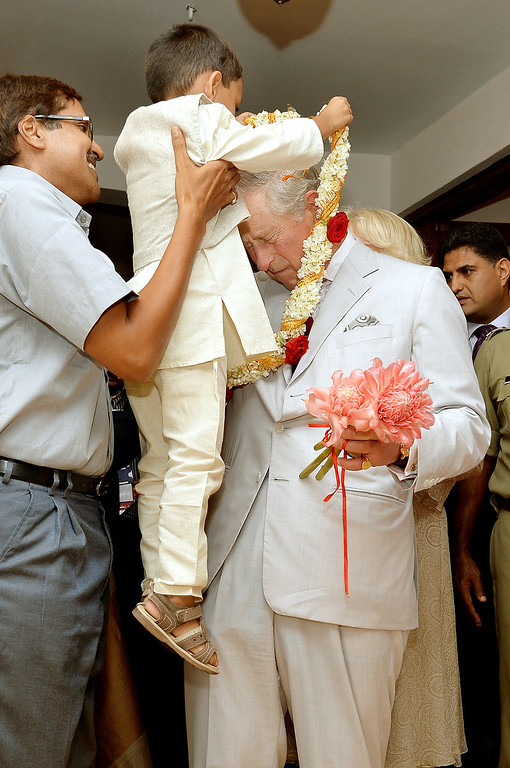 . Prince Charles, Prince of Wales as a garland put on by a small boy being held up by his father in honour of his 65th birthday during a visit to Jew Street in Jew Town on day 9 of an official visit to India on November 14, 2013 in Kochi, India.  (Photo by John Stillwell - Pool/Getty Images)