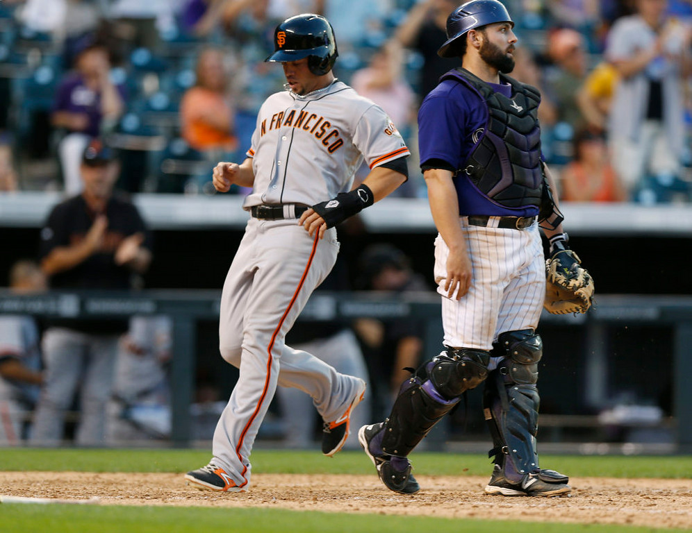 . San Francisco Giants\' pinch-runner Juan Perez, left, scores the tying run on a single by Pablo Sandoval as Colorado Rockies catcher Michael McKenry looks away in the ninth inning of the Rockies\' 10-9 victory in a baseball game in Denver on Monday, Sept. 1, 2014. (AP Photo/David Zalubowski)