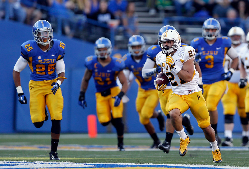 . Wyoming running back Shaun Wick, right, runs against San Jose State during the first half of an NCAA college football game on Saturday, Oct. 26, 2013, in San Jose, Calif. (AP Photo/Marcio Jose Sanchez)