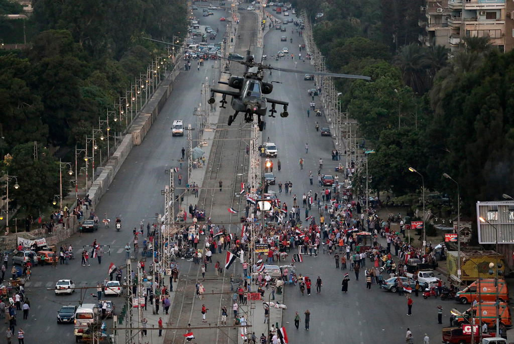 ". Egyptian military attack helicopter flies by the Presidential palace, in Cairo, Egypt, Friday, July 5, 2013. Army troops opened fire Friday on protesters demanding the reinstatement of toppled President Mohammed Morsi, killing at least one, as supporters of the Islamist leader rallied across Egypt chanting ""Down with military rule!\"" (AP Photo/Hassan Ammar)"