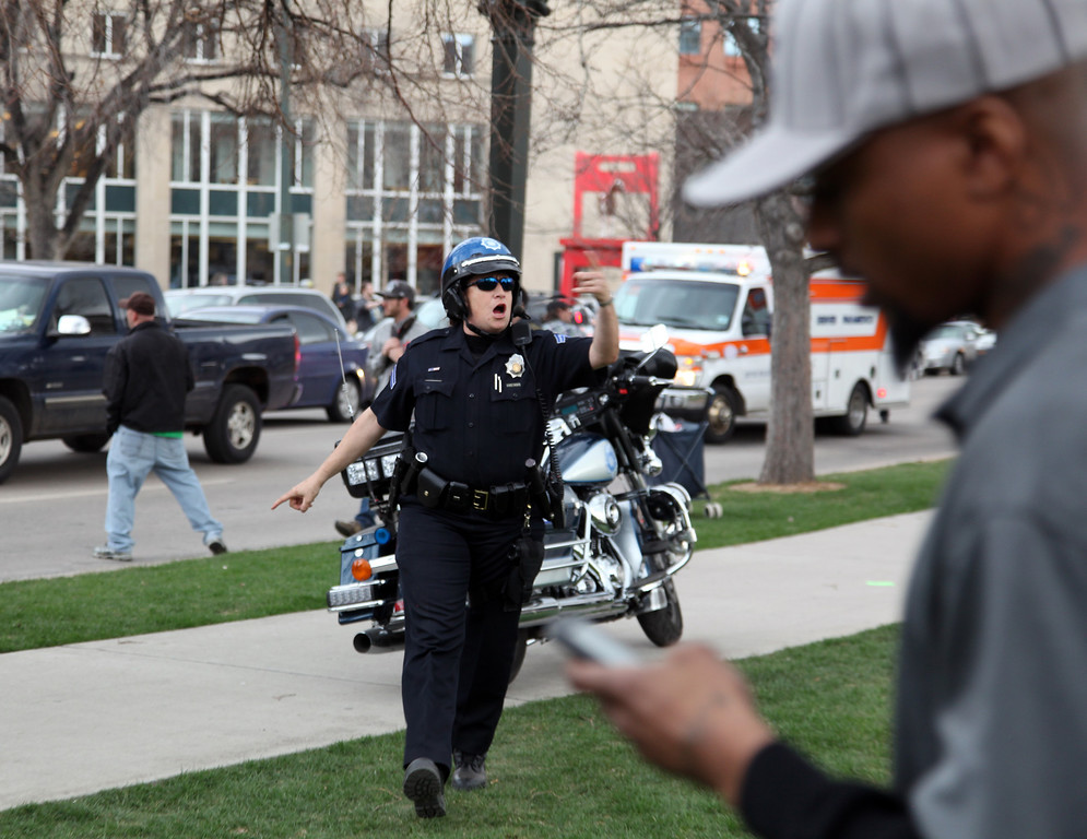 . Denver, CO. - April 20: A Denver Police officer takes control of a crime scene at Civic Center Park in Denver Colorado after a shooting at a 4/20 marijuana rallySaturday afternoon, April 20th, 2013. (Photo By Alex Scott/Special to The Denver Post)