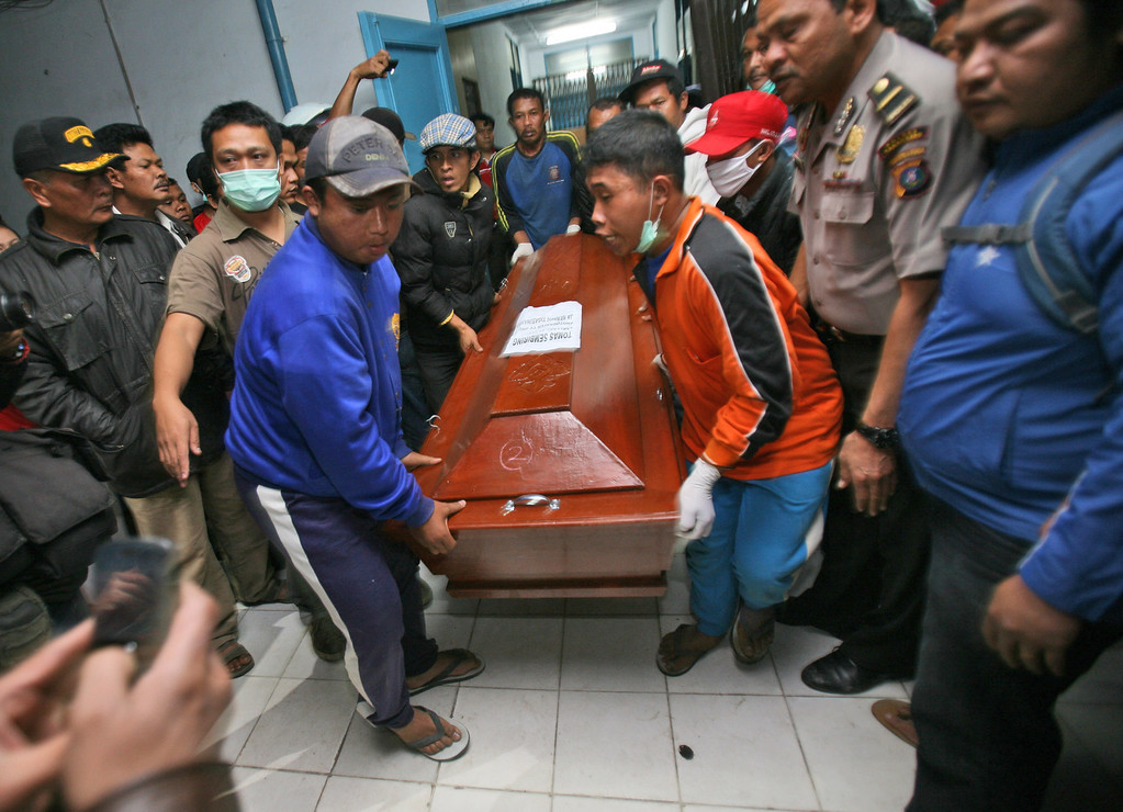 . Relatives carry a coffin containing the body a victim of the eruption of Mount Sinabung, at a hospital in Kabanjahe, North Sumatra, Indonesia, Saturday, Feb. 1, 2014. (AP Photo/Binsar Bakkara)