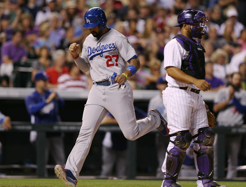 . Los Angeles Dodgers\' Matt Kemp, left, strides across home plate to score the go-ahead run on a single hit by Juan Uribe as Colorado Rockies catcher Wilin Rosario looks away in the ninth inning of the Dodgers\' 3-2 victory in a baseball game in Denver, Thursday, July 3, 2014. (AP Photo/David Zalubowski)