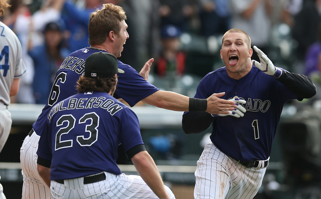 . Colorado Rockies\' Brandon Barnes, right, celebrates driving in the winning run with teammates Charlie Culberson, front left, and Corey Dickerson against the Los Angeles Dodgers in the 10th inning of the Rockies\' 5-4 victory in 10 innings in a baseball game in Denver on Saturday, June 7, 2014. (AP Photo/David Zalubowski)