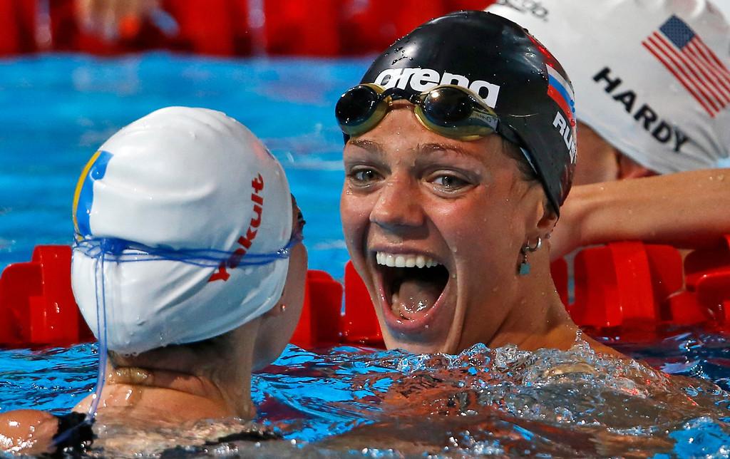 . Russia\'s Yuliya Efimova, right, celebrates with Ukraine\'s Mariia Liver after winning her Women\'s 50m breaststroke heat in a new world record time of 29.78 at the FINA Swimming World Championships in Barcelona, Spain, Saturday, Aug. 3, 2013. (AP Photo/Daniel Ochoa de Olza)