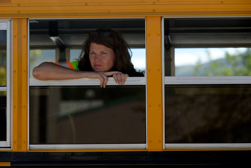 . LYONS, CO. - SEPTEMBER 18: Town administrator Victoria Simonsen looks over damage from a bus while touring Lyons,  CO September 18, 2013. Business owners were allowed to return to town today and residents will be allowed to visit their homes tomorrow. As emergency personnel methodically make their way from door-to-door of flooded and damaged homes this week, the number of unaccounted-for Coloradans is dropping. The number in Boulder County has fallen to four. (Photo By Craig F. Walker / The Denver Post)