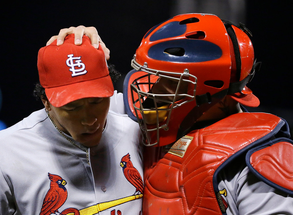 . St. Louis Cardinals relief pitcher Carlos Martinez, left, and catcher Yadier Molina react during the eighth inning of Game 2 of baseball\'s World Series against the Boston Red Sox Thursday, Oct. 24, 2013, in Boston. (AP Photo/Matt Slocum)
