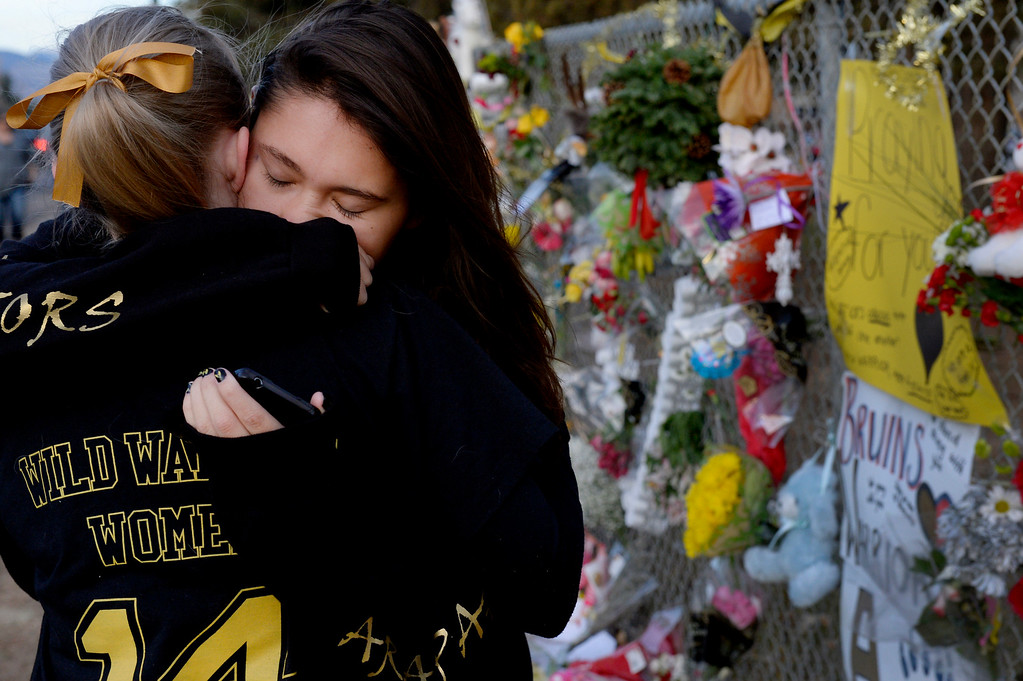""". Seniors Lexi Barrent, right, and Melissa Tombaugh embrace at the tribute area before entering  Arapahoe High School in Centennial, CO December 19, 2013. Seniors and Juniors returned to the school for two hour periods Thursday, Sophomores and Freshmen will return on Friday. Lexi said, \""""I\'m a little nervous, you have to get used to it again.\"""" The victim from Friday�s shooting at Arapahoe High School, Claire Davis, 17, remains in critical condition. She was shot on Friday when classmate Karl Pierson opened fire in the school. The gunman died from a self-inflicted gunshot wound. (Photo By Craig F. Walker / The Denver Post)"""