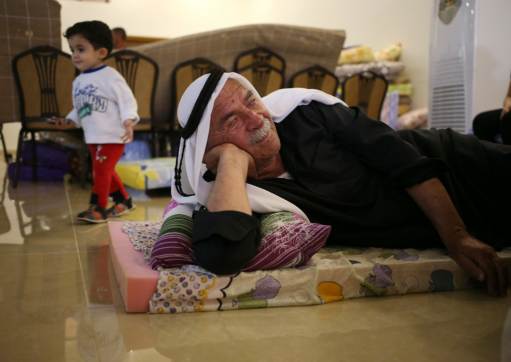 . A displaced Iraqi Christian man who fled from the Christian village of Hamdania near Mosul province in Iraq, lies on a mattress where he settled with his family at a church hall that turned for the displaced Christian families, in Ainkawa, a suburb of Irbil, with a majority Christian population, Iraq, Friday, June 27, 2014. TAround 2,000 Christians had entered the Kurdish city of Irbil by Thursday morning, June 26. A Christian official there said the Kurdish region is the only part of Iraq where Christians are protected from violence. (AP Photo/Hussein Malla)