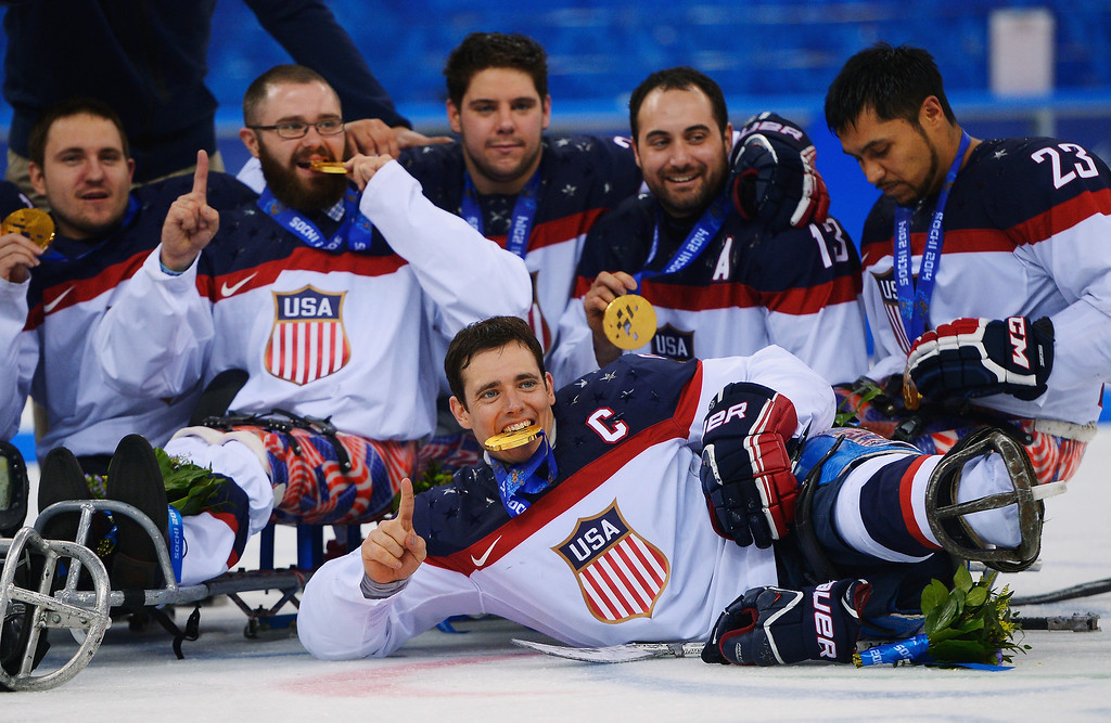 . Andy Yohe of the United States (front) poses with team mates after winning the gold medal in the Ice Sledge Hockey Gold Medal game between the United States and Russia on day eight of the Sochi 2014 Paralympic Winter Games at Shayba Arena on March 15, 2014 in Sochi, Russia.  (Photo by Dennis Grombkowski/Getty Images)
