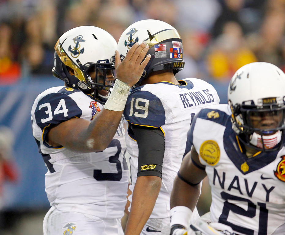 . Navy fullback Noah Copeland (34) is congratulated by quarterback Keenan Reynolds (19) after scoring a touchdown against Army during the second quarter of the Army versus Navy NCAA football game in Philadelphia, Pennsylvania, December 8, 2012. REUTERS/Tim Shaffer