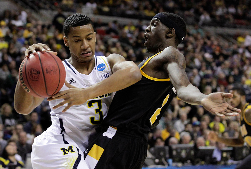 . Michigan Wolverines Trey Burke drives on VCU Rams Briante Weber during the first half of their third round NCAA tournament basketball game in Auburn Hills, Michigan March 23, 2013. REUTERS/Jeff Kowalsky