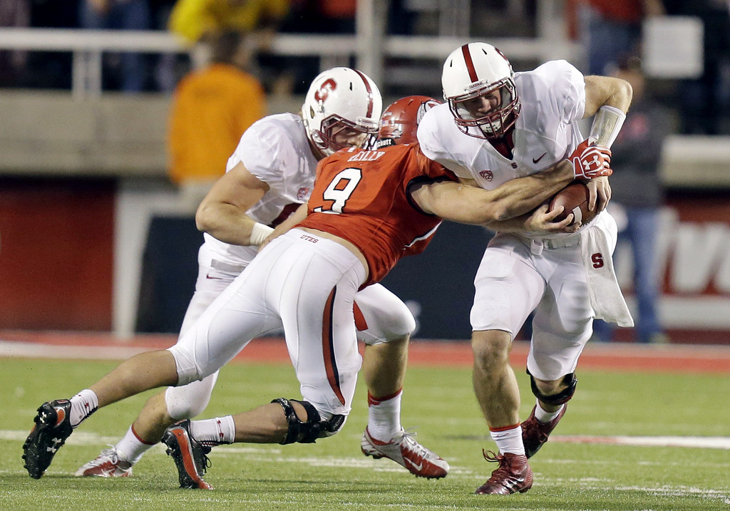 . Utah\'s Trevor Reilly (9) tackles Stanford quarterback Kevin Hogan, right, during the fourth quarter of an NCAA college football game on Saturday, Oct. 12, 2013, in Salt Lake City. (AP Photo/Rick Bowmer)
