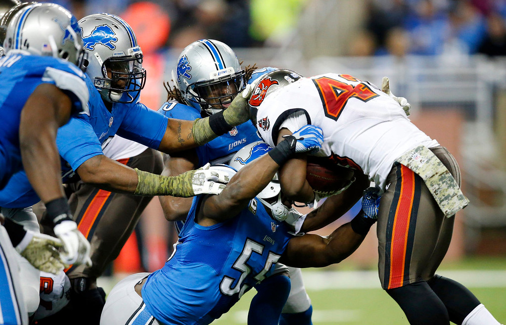 . The Detroit Lions defensive line takes down Tampa Bay Buccaneers running back Bobby Rainey (43) during the third quarter of an NFL football game at Ford Field in Detroit, Sunday, Nov. 24, 2013. (AP Photo/Rick Osentoski)
