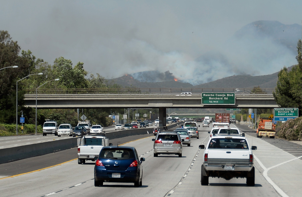 . Cars travel on the 101 Freeway as a wildfire burns in the hills nearby on May 2, 2013 in Newbury Park, California. Winds have made fighting the blaze, called the Springs Fire, more difficult and authorities have ordered some mandatory evacuations in the area. (Photo by Kevork Djansezian/Getty Images)