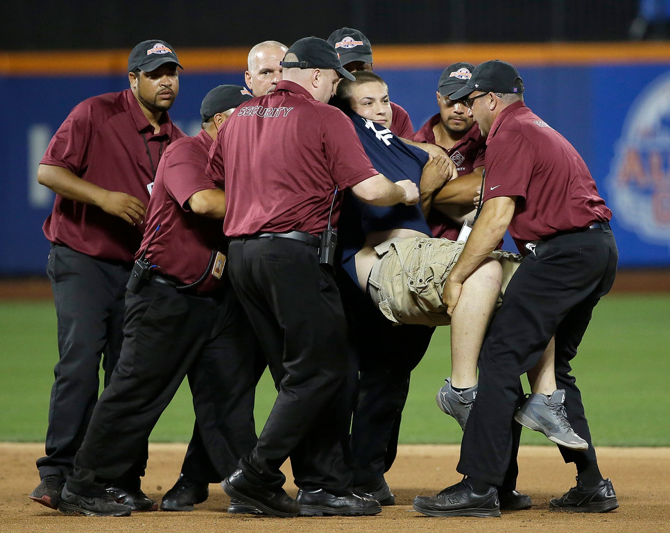 . A spectator is carried by security personnel after he ran onto the field during the fifth inning of the MLB All-Star baseball game, on Tuesday, July 16, 2013, in New York. (AP Photo/Matt Slocum)