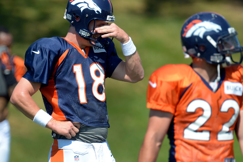 . Denver Broncos quarterback Peyton Manning (18) wipes the sweat from his eyes during drills at practice August 20, 2013 at Dove Valley (Photo by John Leyba/The Denver Post)