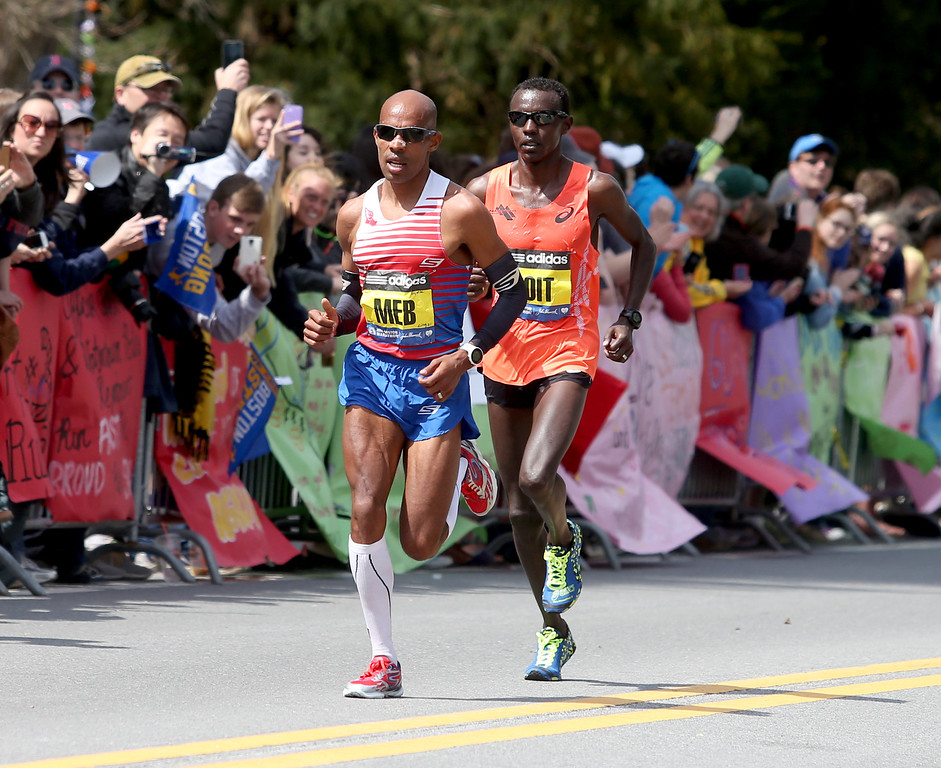 . Meb Keflezighi, of the United States, leads Josphat Boit, also from the United States, passed  Wellesley College during the 118th Boston Marathon Monday, April 21, 2014 in Wellesley. (AP Photo/Mary Schwalm)