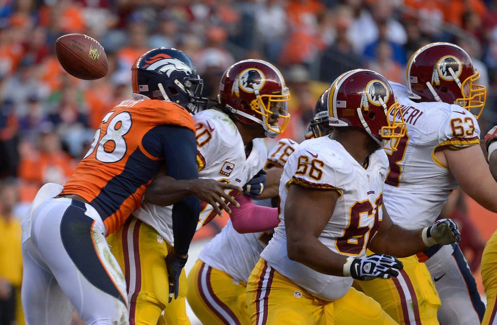 . Denver Broncos outside linebacker Von Miller (58) hits Washington Redskins quarterback Robert Griffin III (10) from behind causing a fumble during the fourth quarter. The Denver Broncos vs. the Washington Redskins at Sports Authority Field at Mile High in Denver on October 27, 2013. (Photo by Tim Rasmussen/The Denver Post)