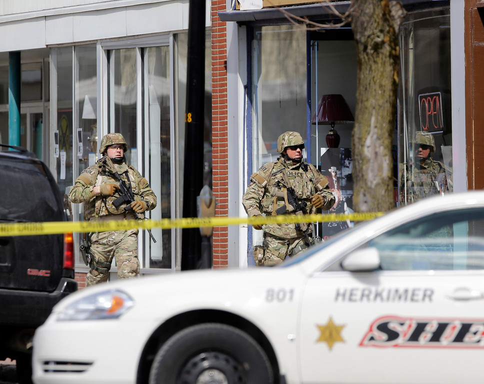 . Law enforcement officers walk along Main Street in Herkimer, N.Y., while searching for a suspect in two shootings that killed four and injured at least two on, Wednesday, March 13, 2013.   (AP Photo/Mike Groll)