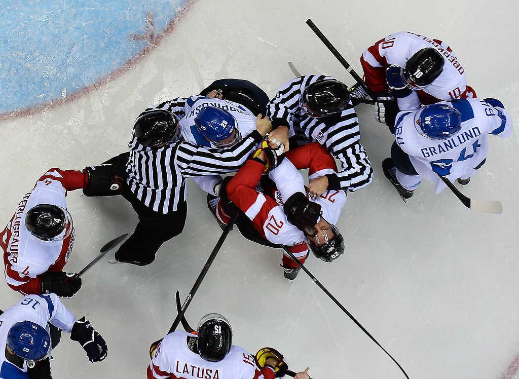. Finland\'s Lauri Korpikoski (Top C) punches Austria\'s Daniel Welser during the Men\'s Ice Hockey Group B match Finland vs Austria at the Bolshoy Ice Dome during the Sochi Winter Olympics on February 13, 2014.   VALEXANDER NEMENOV/AFP/Getty Images
