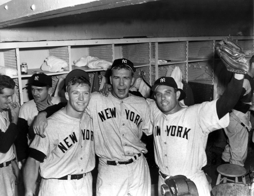 . Left-handed hurler Bob Kuzava is flanked by Mickey Mantle, left, and Gene Woodling in the New York Yankees locker room after their 4-2 win over the Brooklyn Dodgers in the seventh and final game of the World Series at Ebbets Field in Brooklyn, N.Y., Oct. 7, 1952.  Kuzava was relief pitcher in the seventh inning.  Mantle homered in the 6th inning and Woodling in the 5th inning.  (AP Photo)