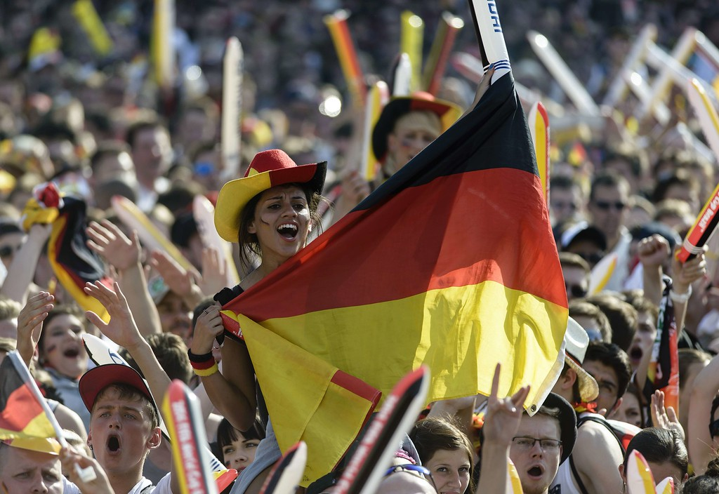 . TOPSHOTS A fan holds the German flag as she watches on a giant screen the FIFA World Cup 2014 quarter-final football match between Germany and France, Germany on July 4, 2014 in Berlin. AFP PHOTO / CLEMENS BILANCLEMENS BILAN/AFP/Getty Images