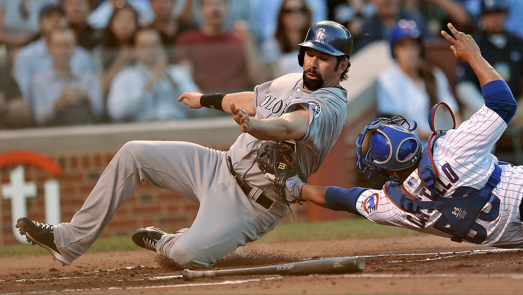 . Colorado Rockies\' Todd Helton left, is tagged out by Chicago Cubs catcher Welington Castillo at home plate during the second inning of a baseball game in Chicago, Tuesday, May 14, 2013. (AP Photo/Paul Beaty)