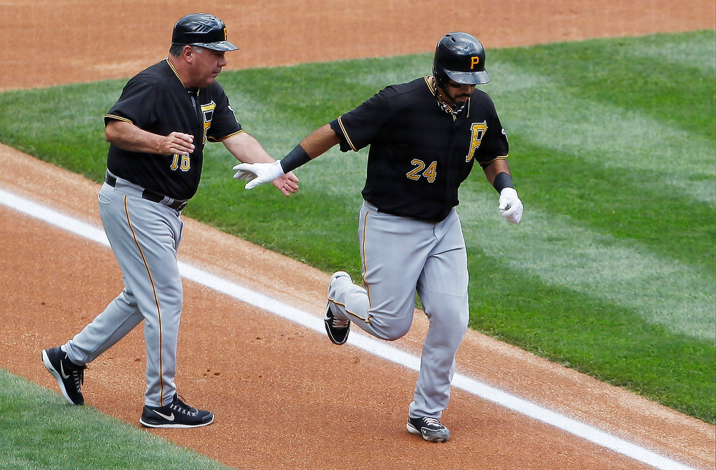 . Pittsburgh Pirates third base coach Nick Leyva, left, congratulates Pedro Alvarez as he circles the bases after hitting a solo home run against the Colorado Rockies to lead of the top of the second inning a baseball game in Denver on Sunday, Aug. 11, 2013. (AP Photo/David Zalubowski)