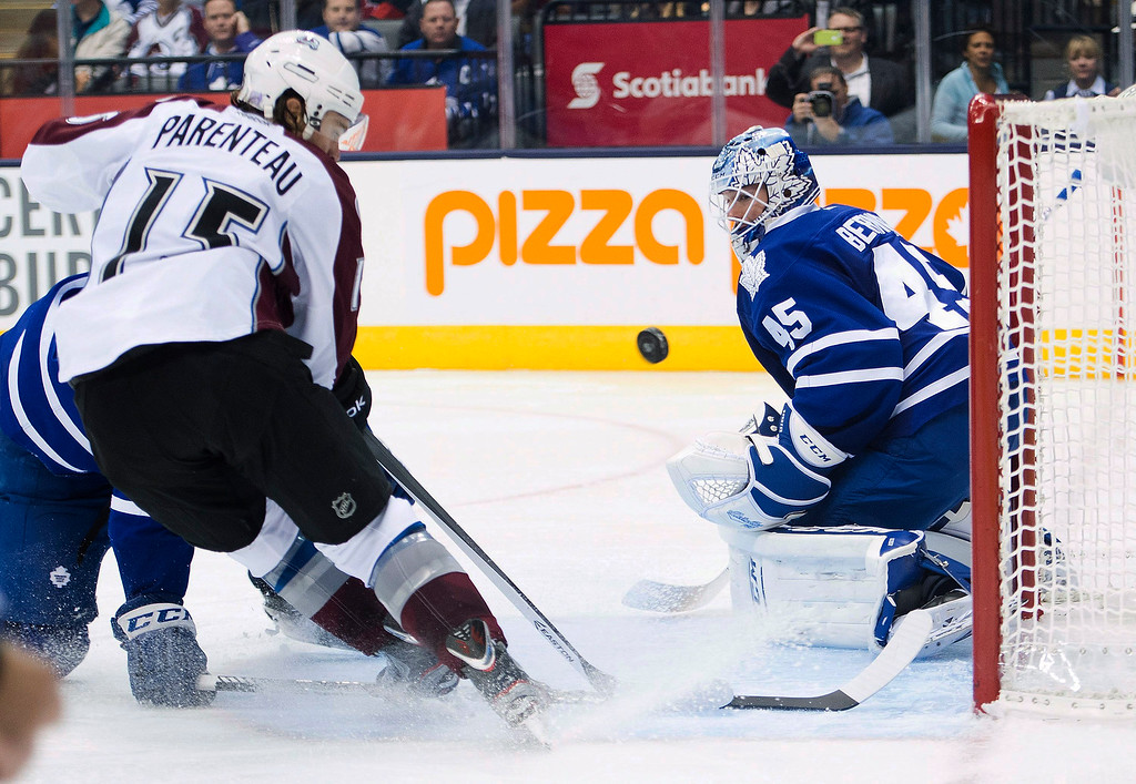 . Colorado Avalanche forward PA Parenteau, left, scores the game-winning goal past Toronto Maple Leafs goalie Jonathan Bernier, right, during the third period of an NHL hockey game in Toronto on Tuesday, Oct. 8, 2013. Colorado won 2-1. (AP Photo/The Canadian Press, Nathan Denette)