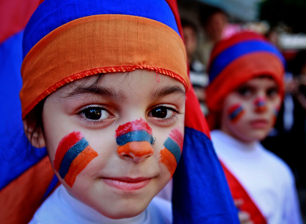 . Lebanese Armenian boys, their faces painted with colors of the Armenian flag, attend a rally marking the 98th anniversary of massacres on thousands of Armenians, in Beirut, Lebanon, Wednesday, April 24, 2013. Armenian communities around the world mark the killing of up to 1.5 million Armenians, on April 24 each year with marches, vigils and rallies to demand recognition from the world community, and reparations from Turkey. Turkey claims the number of deaths is inflated and says the victims were killed in civil unrest. (AP Photo/Bilal Hussein)