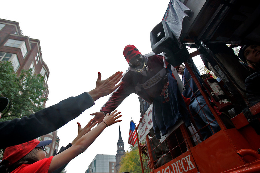 . Boston Red Sox\' David Ortiz slaps hands with fans as the parade of duck boats ride along Boylston Street in Boston, Saturday, Oct 30, 2004. Hundreds of thousands of Red Sox fans jammed streets and the banks of the Charles River on Saturday to watch a parade many had begun to doubt they would ever witness: a toast to a World Series champion team. (AP Photo/Elise Amendola)