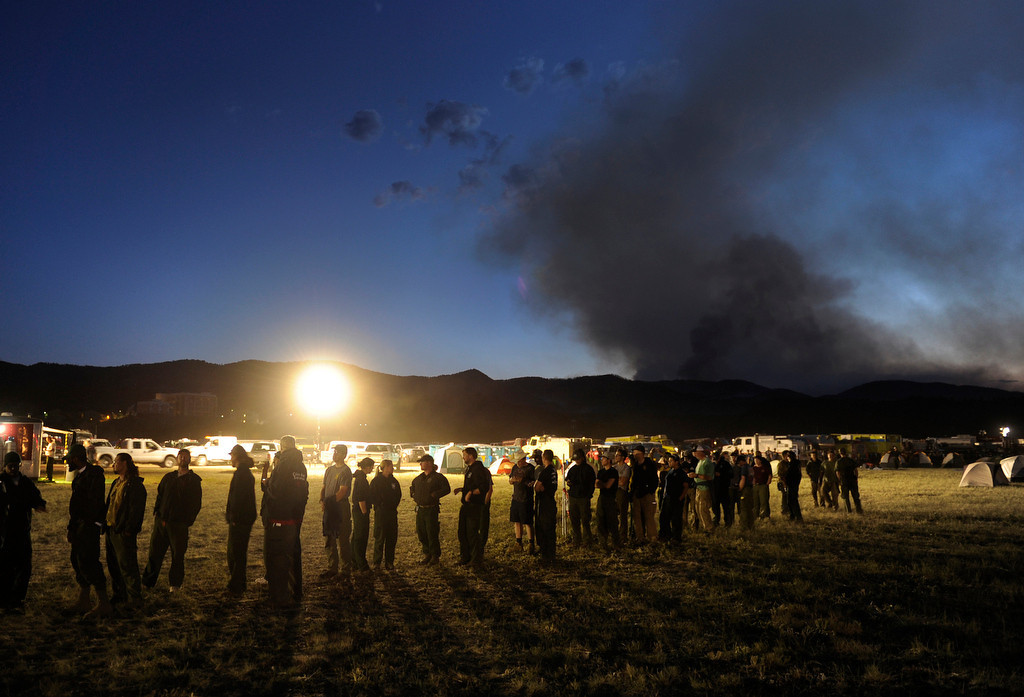 . Hundreds of firefighters lined up to grab a late dinner Wednesday night, June 13, 2012 after a long day working the High Park fire.  Smoke continued to billow into the night sky, visible in the distance from the Incident Command Post, where the firefighters are sleeping overnight. Karl Gehring/The Denver Post