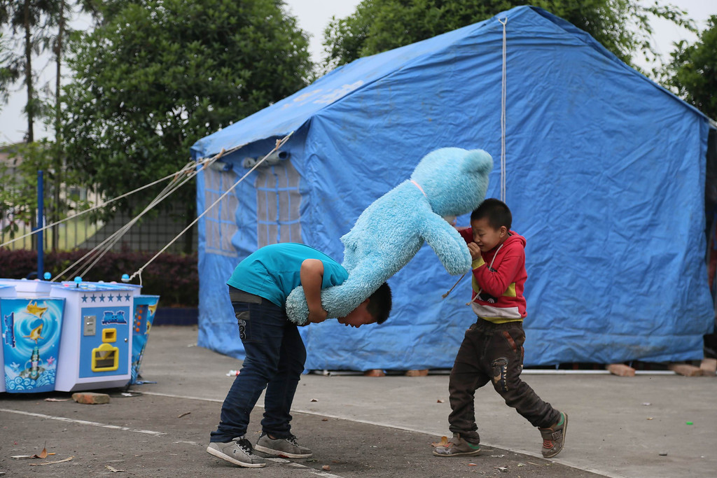 . This photo taken on April 21, 2013 shows two kids playing with a doll in a temporary settlement in the disaster-hit area of the city of Ya\'an, southwest China\'s Sichuan province.    STR/AFP/Getty Images