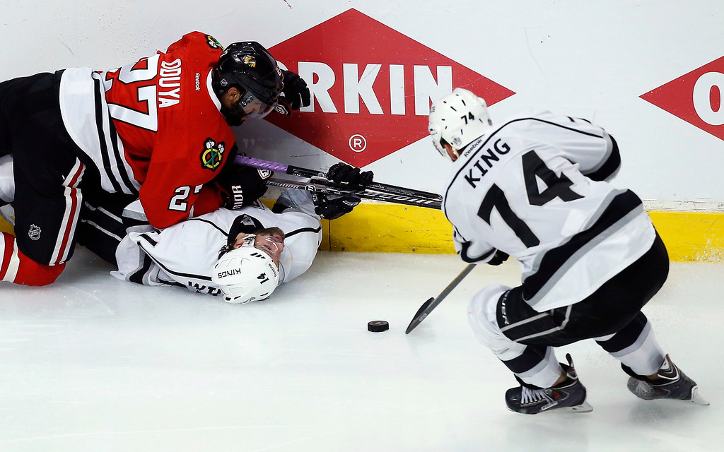 . Los Angeles Kings left wing Dwight King (74) takes the puck as Chicago Blackhawks defenseman Johnny Oduya (27) and the Kings right wing Justin Williams (14) battle during the overtime period in Game 5 of the Western Conference finals in the NHL hockey Stanley Cup playoffs Wednesday, May 28, 2014, in Chicago. (AP Photo/Andrew A. Nelles)