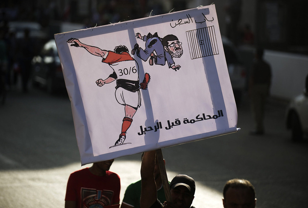 ". An Egyptian protester holds a cartoon depicting President Mohamed Morsi being kicked into prison and reading ""Trial before ouster\"" on his way to join thousands protesting against Morsi and the Muslim Brotherhood at Tahrir Square in Cairo on June 30, 2013. Egyptians flooded the streets determined to oust Morsi on the anniversary of his turbulent first year in power, in the biggest protests Egypt has seen since the 2011 revolt.  GIANLUIGI GUERCIA/AFP/Getty Images"