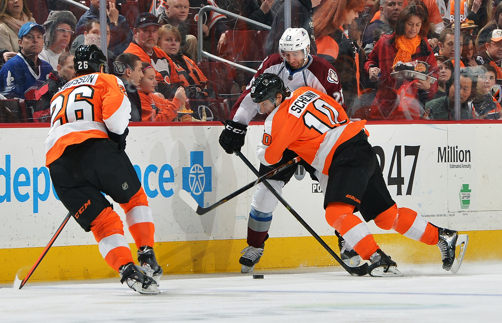 . PHILADELPHIA, PA - FEBRUARY 06: Brayden Schenn #10 of the Philadelphia Flyers holds off Maxime Talbot #25 of the Colorado Avalanche as Erik Gustafsson #26 waits for the puck at the Wells Fargo Center on February 6, 2014 in Philadelphia, Pennsylvania.  (Photo by Drew Hallowell/Getty Images)