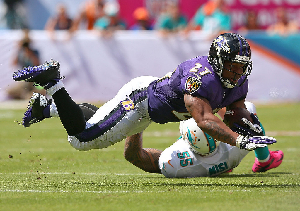 . Ray Rice #27 of the Baltimore Ravens is tackled by Koa Misi #55 of the Miami Dolphins during a game  at Sun Life Stadium on October 6, 2013 in Miami Gardens, Florida.  (Photo by Mike Ehrmann/Getty Images)