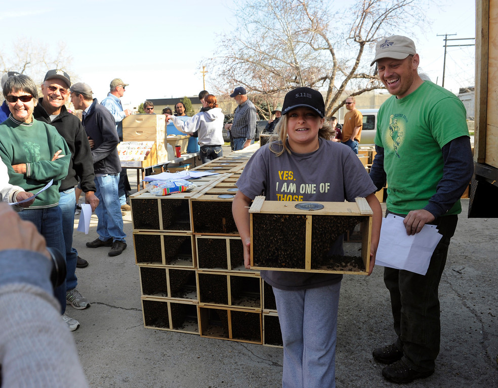 . DENVER, CO - MAY 4: Chad Ragland, right, owner of Apis Hive Co. hands off bees to bee newcomer Grace Fenstermacher, 11, from Littleton, CO. About 300 backyard beekeepers are on hand to pick up their package bees from Apis Hive Co. out of Grand Junction, CO. Each package contains about 10,000 workers and drones as well as one queen. (Photo By Kathryn Scott Osler/The Denver Post)