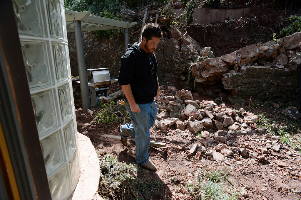 . ELDORADO SPRINGS, CO - SEPTEMBER 18: Danny Knecht walks through the rubble behind his parents home in Eldorado Springs Colorado, Wednesday September 18, 2013. A landslide, caused by last weeks flooding came crashing down, a ditch stopped most of the slide, but a retaining wall crashed down allowing a steam of water into his parents home, flooding most of the house. (Photo By Andy Cross/The Denver Post)