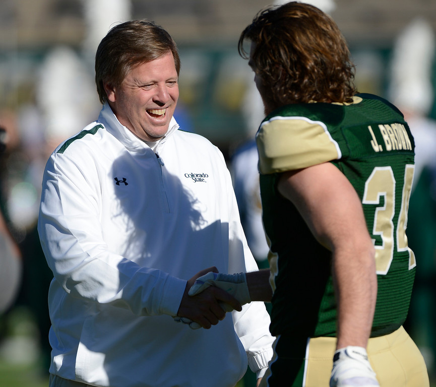 . Colorado State head coach, jim McElwain, greets player, Joe Brown during a pre-game ceremony to honor outgoing seniors at Hughes Stadium before the game against Air Force  Saturday afternoon, November 30, 2013. (Photo By Andy Cross/The Denver Post)