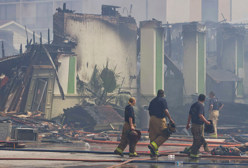 . Firefighters walk through the scene of a fire where four firefighters were killed battling a five-alarm blaze at a restaurant and hotel in southwest Houston May 31, 2013.     REUTERS/Richard Carson