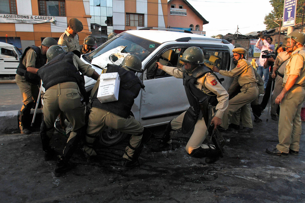 . Indian policemen try to move a car that was fired upon by paramilitary troops when the driver allegedly failed to stop the car at a police barricade in Srinagar, India, Saturday, Sept. 7, 2013. A protest erupted Saturday after Indian police said they killed two alleged militants and two civilians in the disputed Himalayan territory of Kashmir, while authorities maintained tight security for a classical music concert being staged amid separatist objections. The driver was hospitalized in critical condition. (AP Photo/Mukhtar Khan)