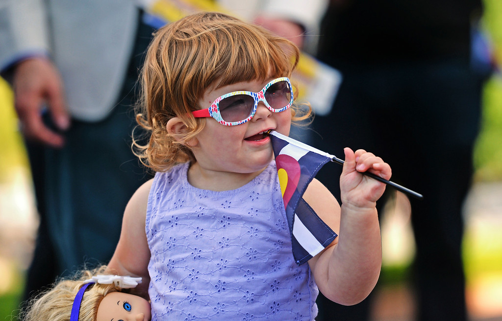 . Greta Vanderberg-Reynolds, 2, joined others to celebrate the 138th anniversary of the state of Colorado on the west steps of Colorado State Capitol in Denver, August 01, 2014. Greta found the small Colorado flag to be a good tool to use for a teething toddler. The celebration included dancing, a cake, a performance from the Colorado Army National Guard Band, and more. (Photo by RJ Sangosti/The Denver Post)