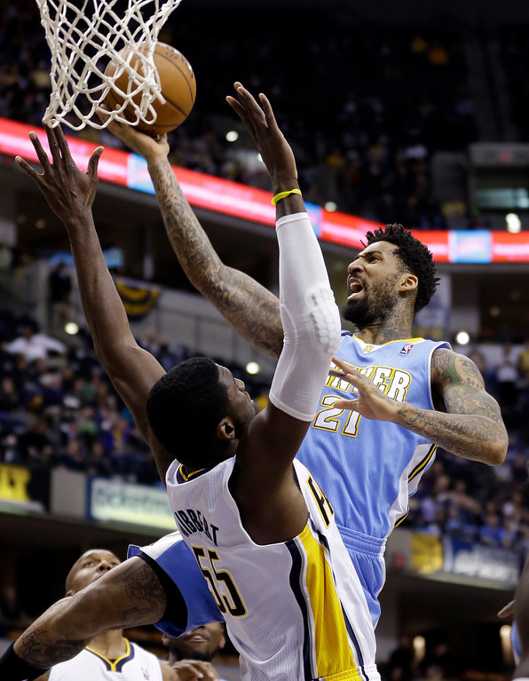 . Denver Nuggets forward Wilson Chandler, right, gets a basket over Indiana Pacers center Roy Hibbert in the first half of an NBA basketball game in Indianapolis, Monday, Feb. 10, 2014. (AP Photo/Michael Conroy)