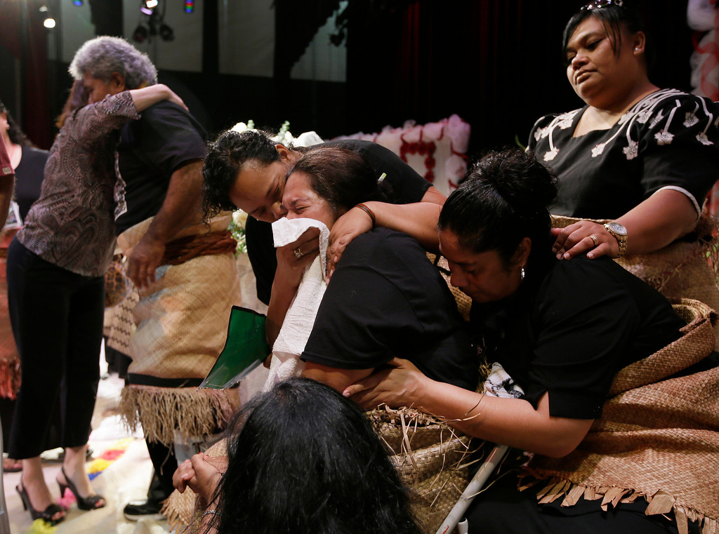 """. Tulima Uhatafe, center, with towel to her face, is consoled by relatives as she and husband Salesi Uhatafe, behind her, receive a line of guest by the caskets of their sons Polo Manukainiu, a Texas A&M redshirt freshman, and Andrew \""""Lolo\"""" Uhatafe, at a memorial service at Trinity High School, Friday, Aug. 9, 2013, in Euless, Texas. More than 2,500 people showed up to mourn the two who were killed in a single car accident in New Mexico, on July 29. Also killed in the accident was 18-year-old Utah recruit Gaius \""""Keio\"""" Vaenuku. (AP Photo/Tony Gutierrez)"""