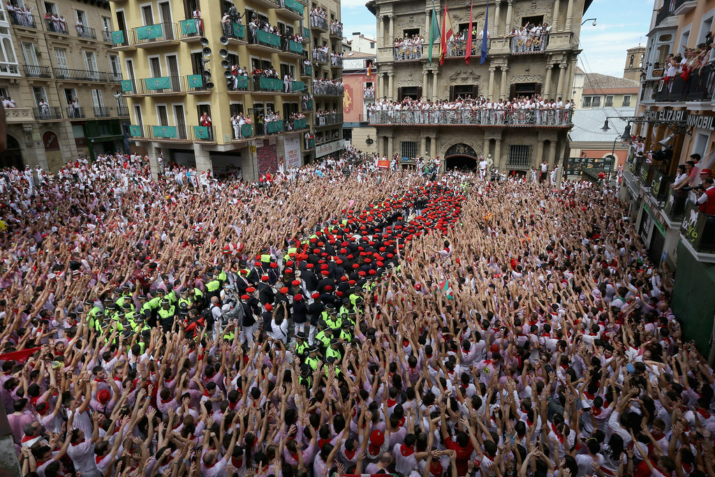 . Revellers wave their arms as the band plays during the opening and the firing of the  \'Chupinazo\' rocket which starts the 2014 Festival of the San Fermin Running of the Bulls on July 6, 2014 in Pamplona, Spain. The annual Fiesta de San Fermin, made famous by the 1926 novel of US writer Ernest Hemmingway entitled \'The Sun Also Rises\', involves the daily running of the bulls through the historic heart of Pamplona to the bull ring.  (Photo by Christopher Furlong/Getty Images)