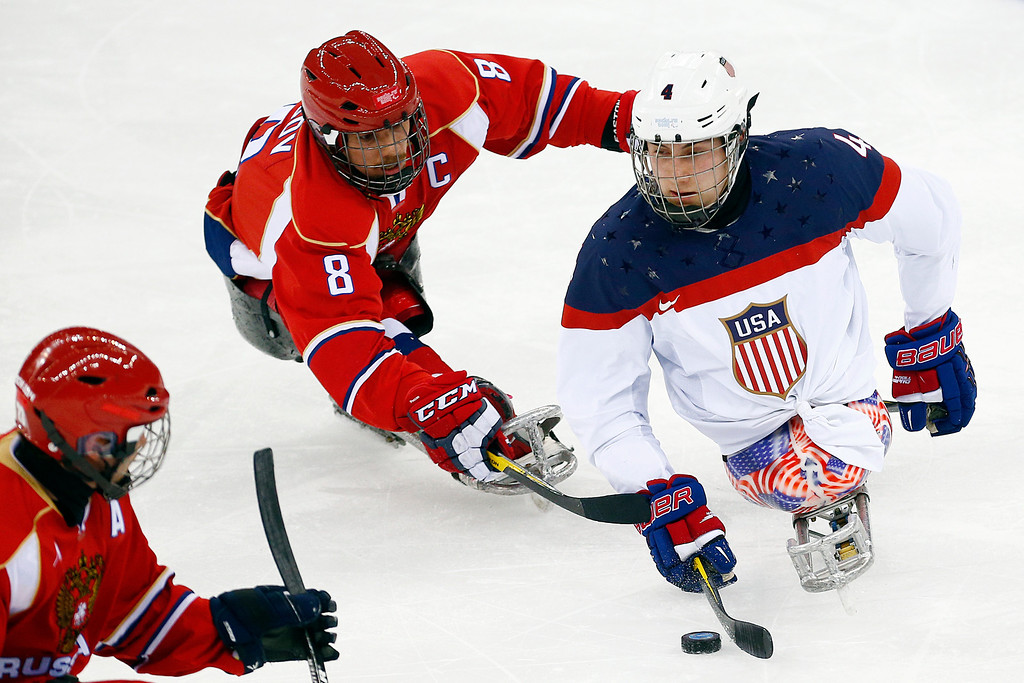 . United States\' Brody Roybal, right in action with Russia\'s Dmitrii Lisov, center during the gold medal ice sledge hockey match between United States and Russia at the 2014 Winter Paralympics in Sochi, Russia, Saturday, March 15, 2014. (AP Photo/Pavel Golovkin)
