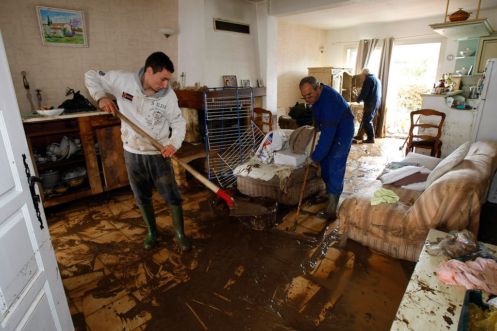 . Victims clean their home after being flooded out, in La Londe Les Maures, near Toulon, southern France, Monday, Jan. 20, 2014, after unusually heavy rains flooded the French Riviera, leaving two people dead and some thousands without electricity or access to roads. The administration for the Var region evacuated some residents and urged others to stay indoors until the waters recede. (AP Photo/Claude Paris)