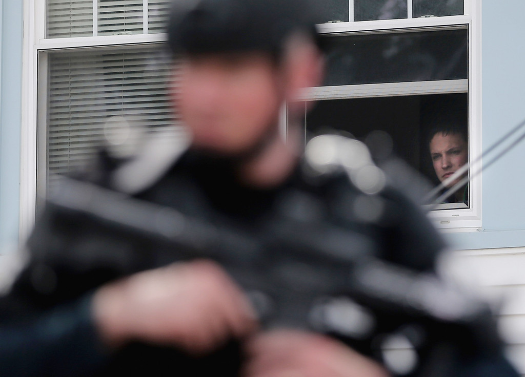 . A person watches from the window of a home as a SWAT team member keeps watch while searching for 19-year-old bombing suspect Dzhokhar A. Tsarnaev on April 19, 2013 in Watertown, Massachusetts. (Photo by Mario Tama/Getty Images)